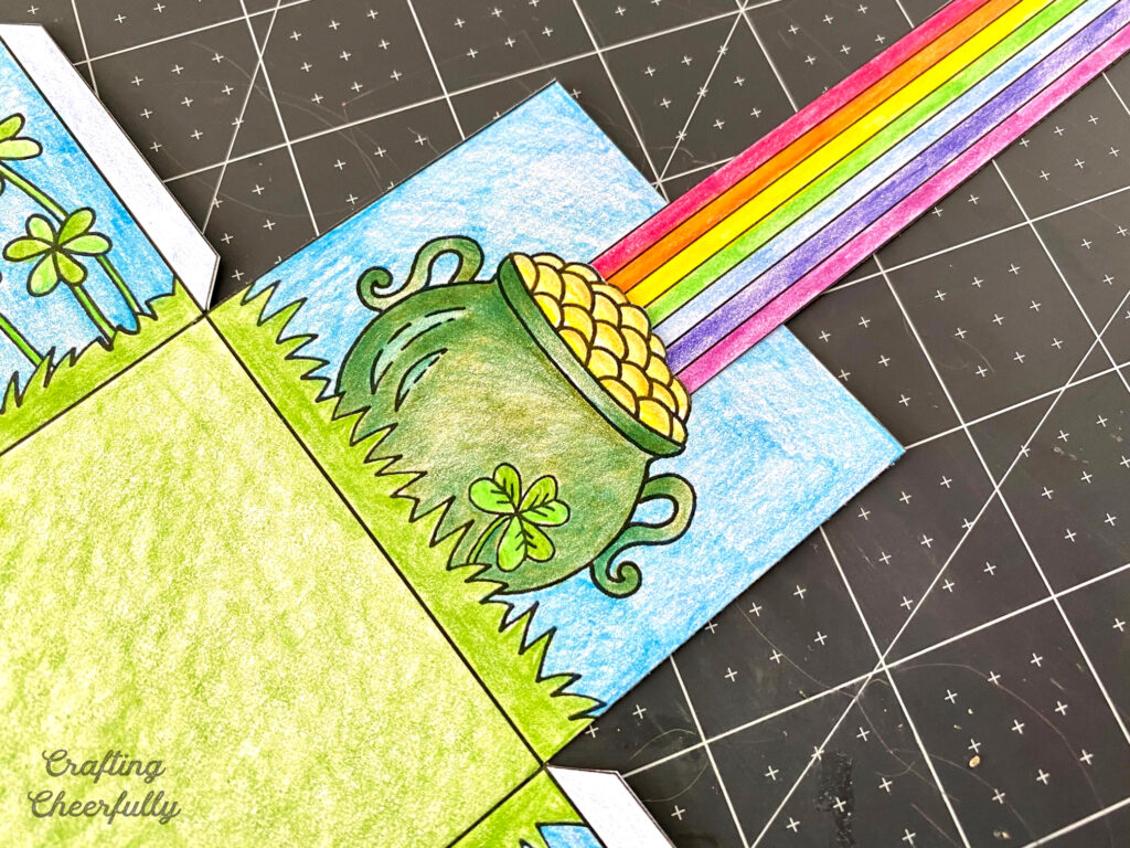The rainbow handle is inserted along the top of the gold coins in the pot of gold drawn on the treat box.