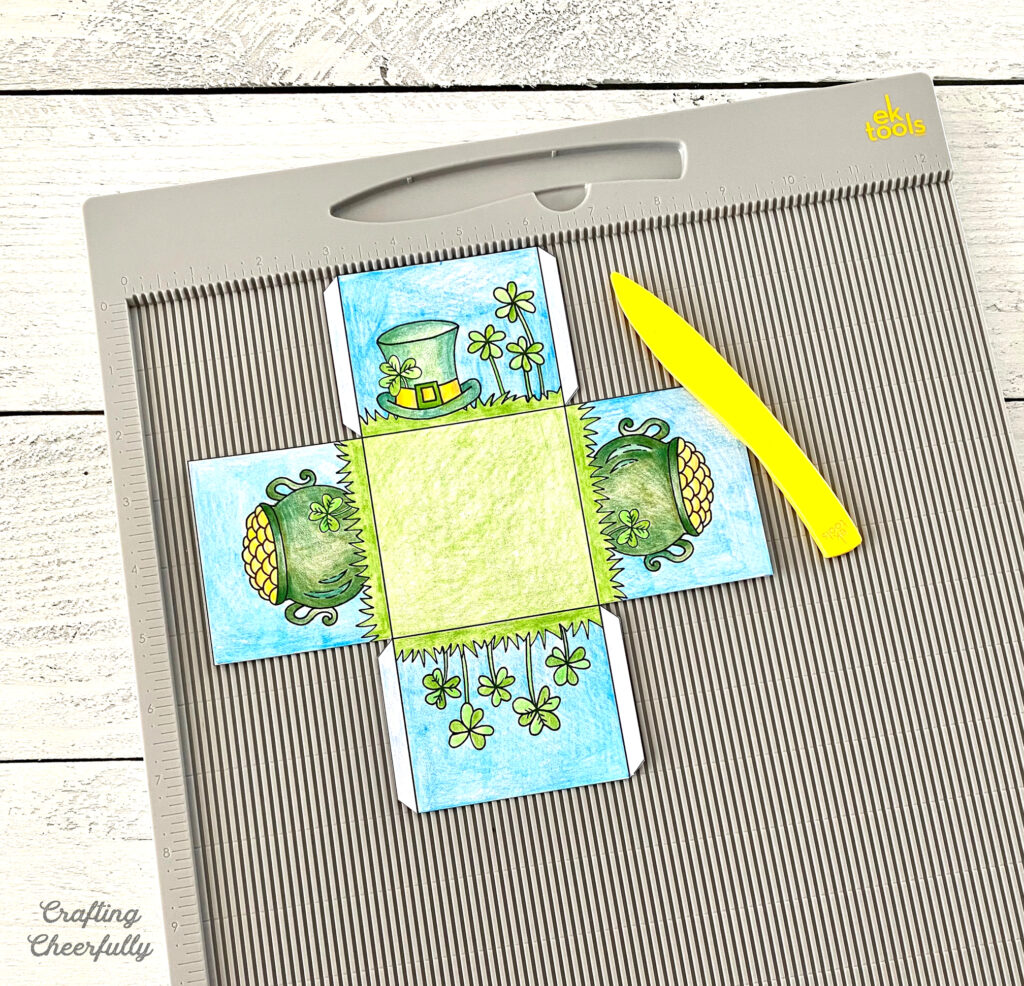 Cut out treat box lays on top of a scoring board with a yellow scoring tool next to it.