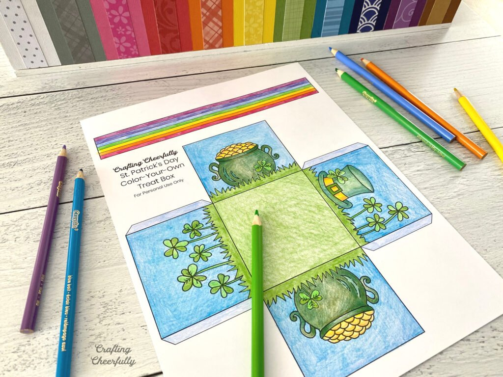 St. Patrick's Day treat box coloring page half-colored lays on a table with colored pencils.