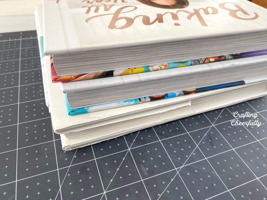 A stack of books sits on a black cutting mat.