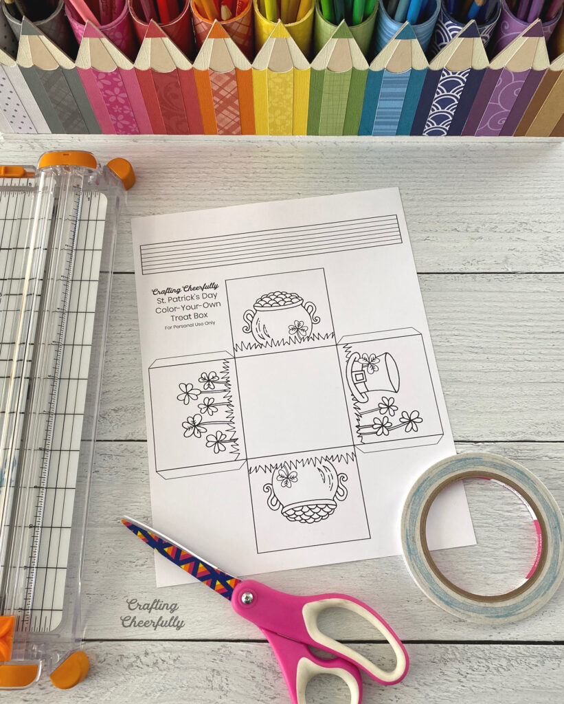 Coloring page for a St. Patrick's Day treat box sits on a table with a scissors, double-sided tape and colored pencils.
