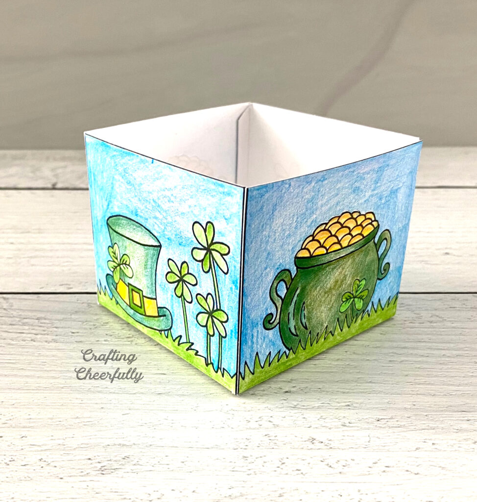 St. Patrick's Day treat box without the handle sits on a wooden table.