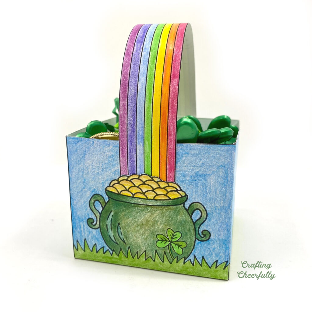 A close up picture of the rainbow handle going into the pot of gold that is drawn on either side of the treat box.