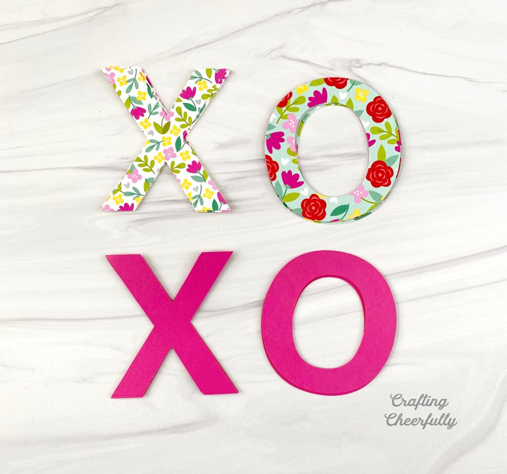 X and O letters cut out of floral paper and pink paper laying on a table.