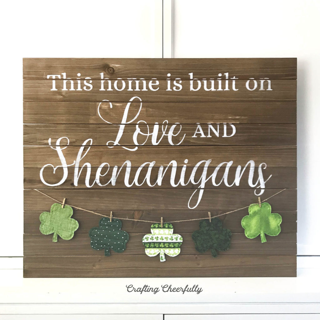 "Wooden sign with the words ""This home is built on Love and Shenanigans"" with a banner of fabric shamrocks hanging on the bottom."