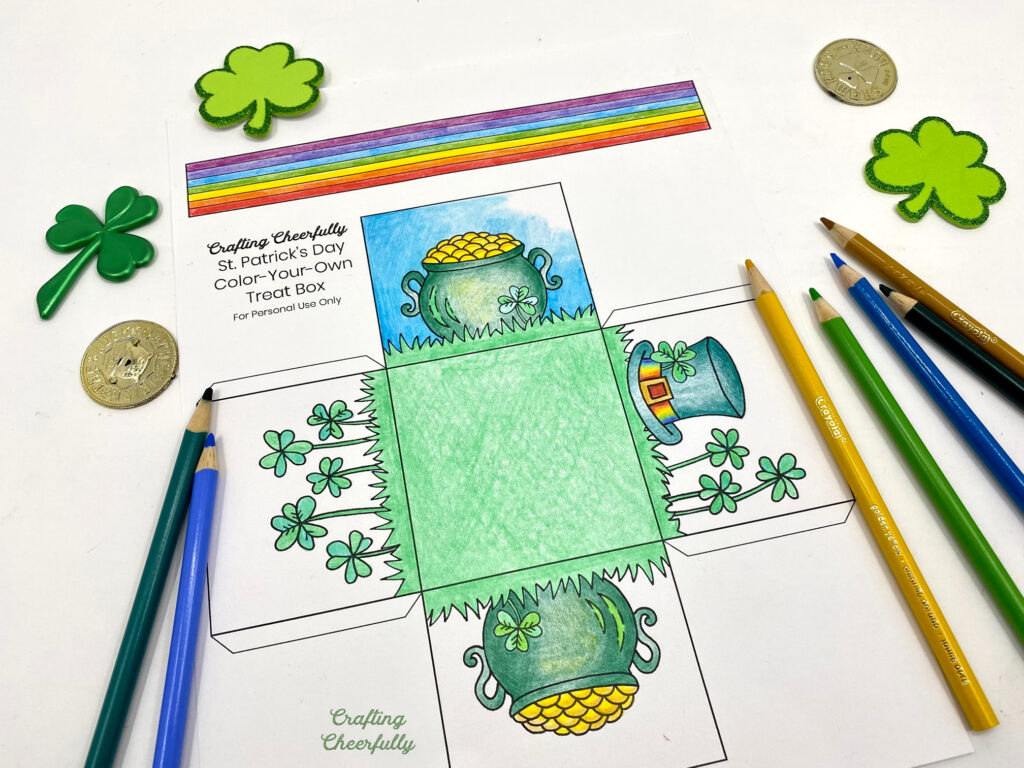 St. Patrick's Day treat box coloring page half-colored lays on a table with colored pencils, gold coins and shamrocks.