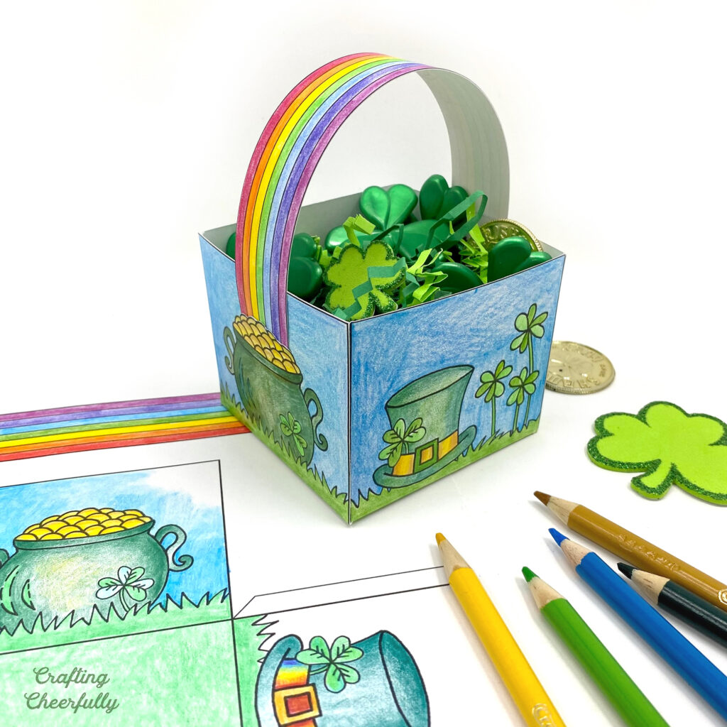 St. Patrick's Day treat box with a rainbow handle sits on a white table with colored pencils and a coloring page next to it.