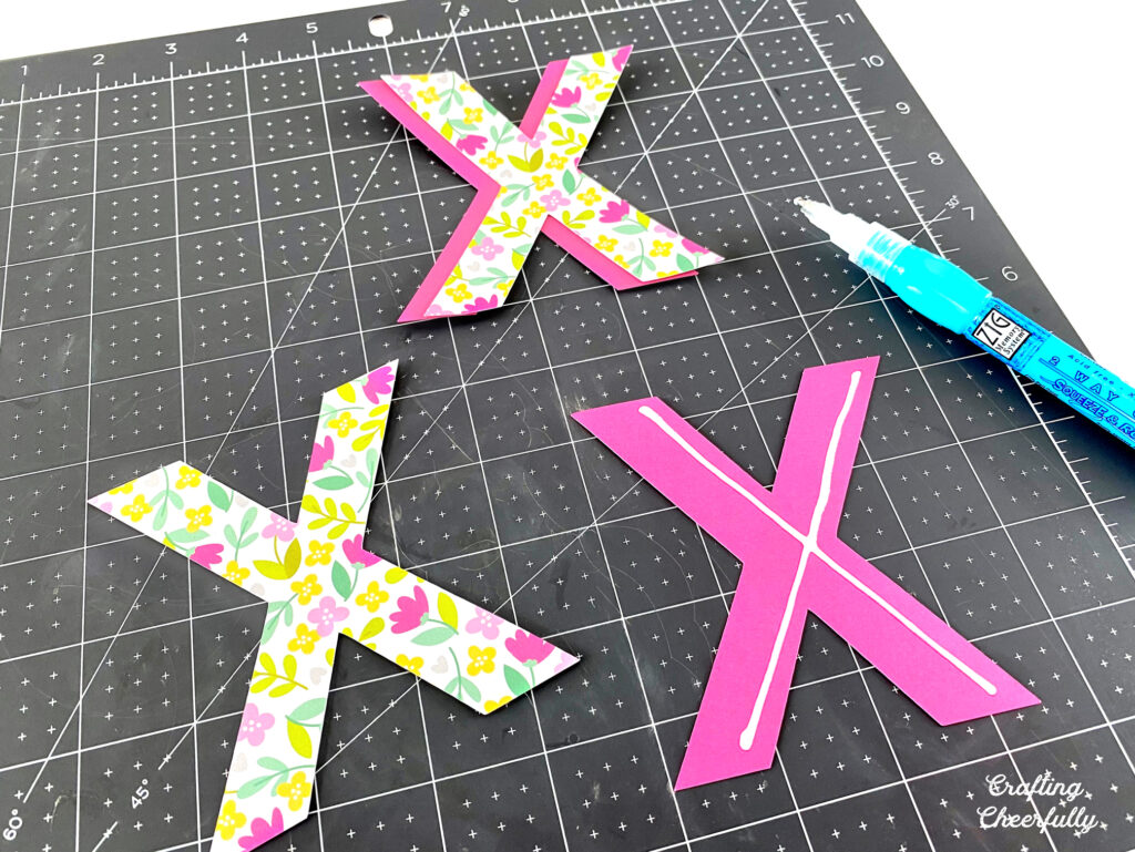 Glue is applied to the X letters so they can be layered.