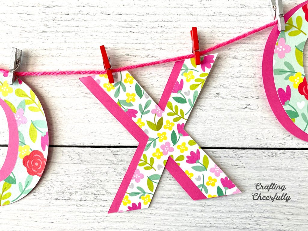 Valentine's Day banner with XO letters clipped to a pink string with mini clothespins.