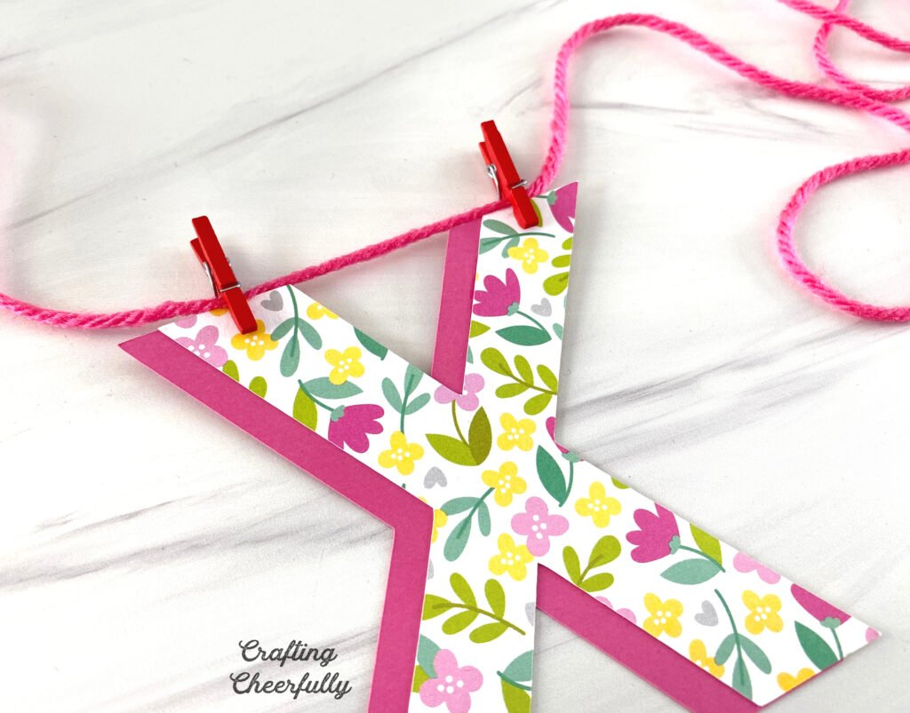 The paper X is attached to pink string using mini red clothespins.