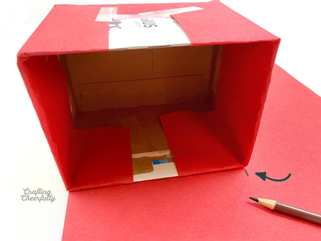 A brown pencil marks a piece of red paper the width of the box.