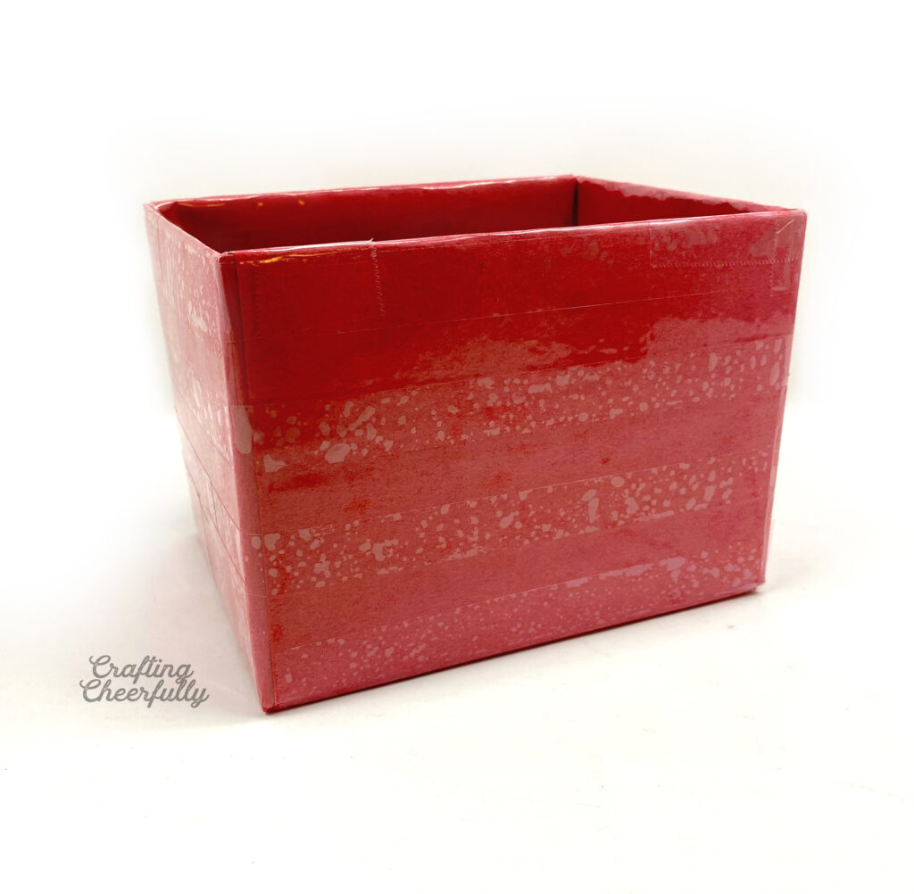 A box is covered in red construction paper and clear packing tape.