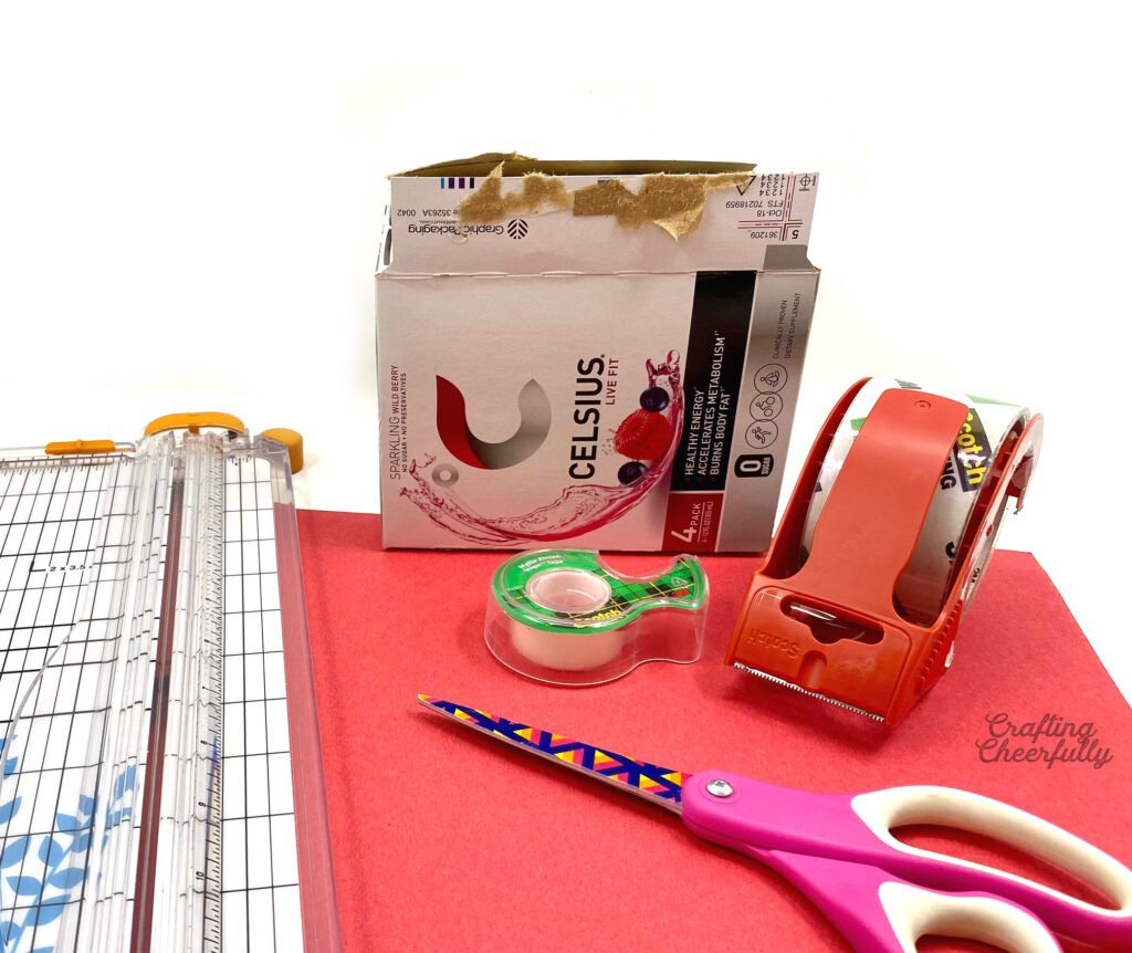 A cardboard box, scissors, tape and red construction paper sit on a table ready to craft with!