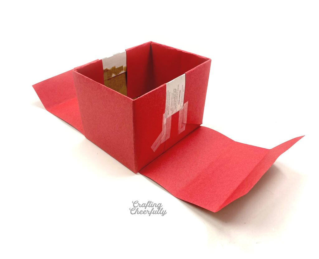 Red paper is pre-folded and ready to be wrapped around the cardboard box.