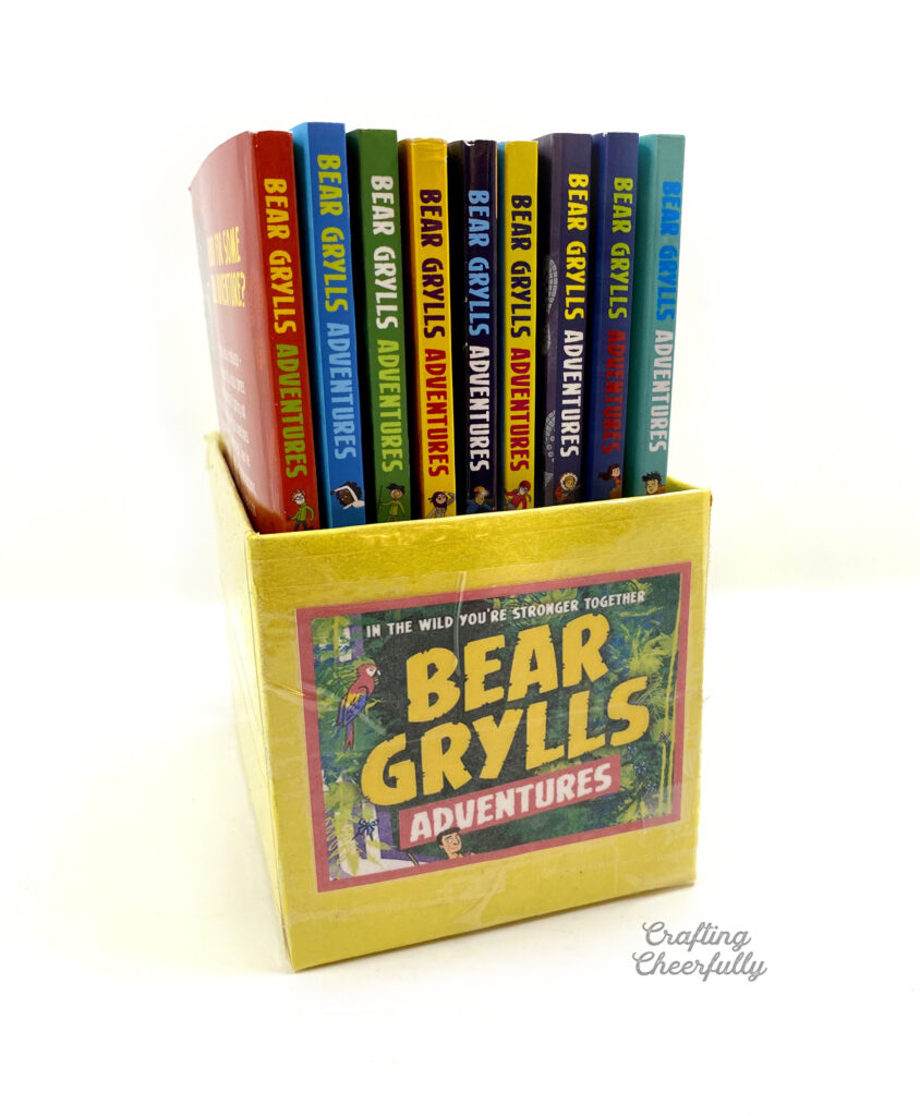 """A yellow book bin filled with """"Bear Grylls"""" books."""
