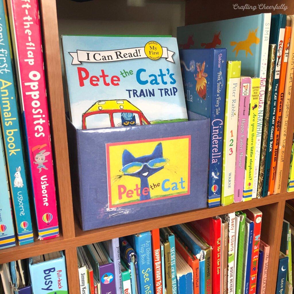 A book bin holding Pete the Cat books sits on a bookshelf.