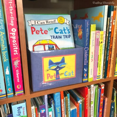 Blue DIY Book bin sits on a book shelf filled with Pete the Cat books.