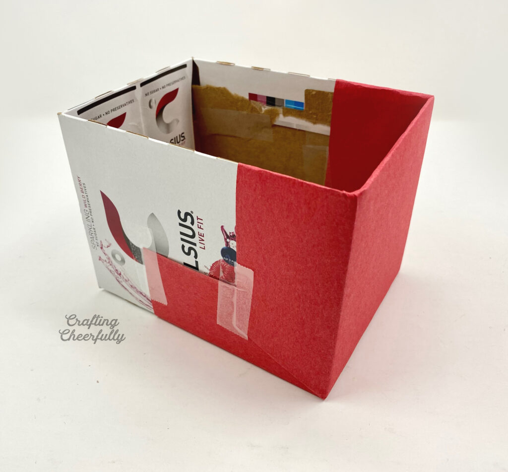 Red paper is taped to one end of the cardboard box.