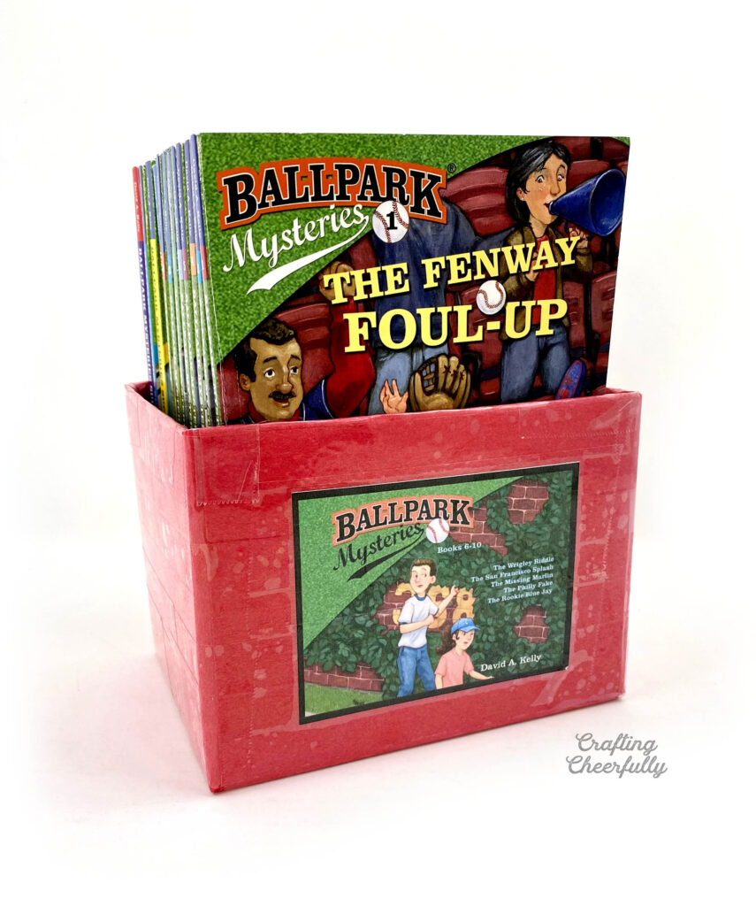 """Red book bin filled with books from the """"Ballpark Mysteries"""" series."""