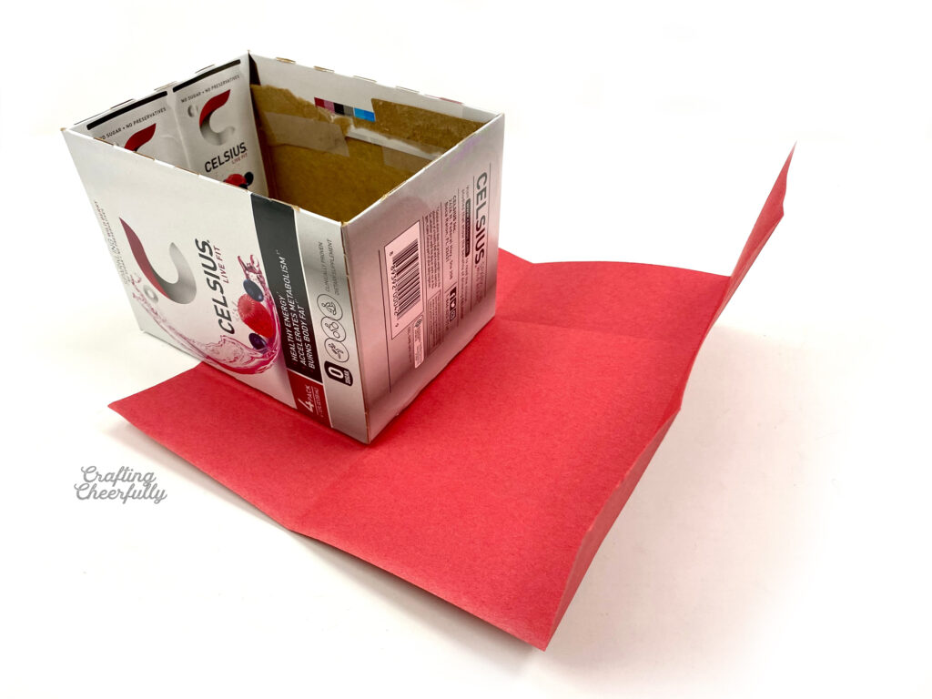 Red paper is pre-folded sitting next to a cardboard box.