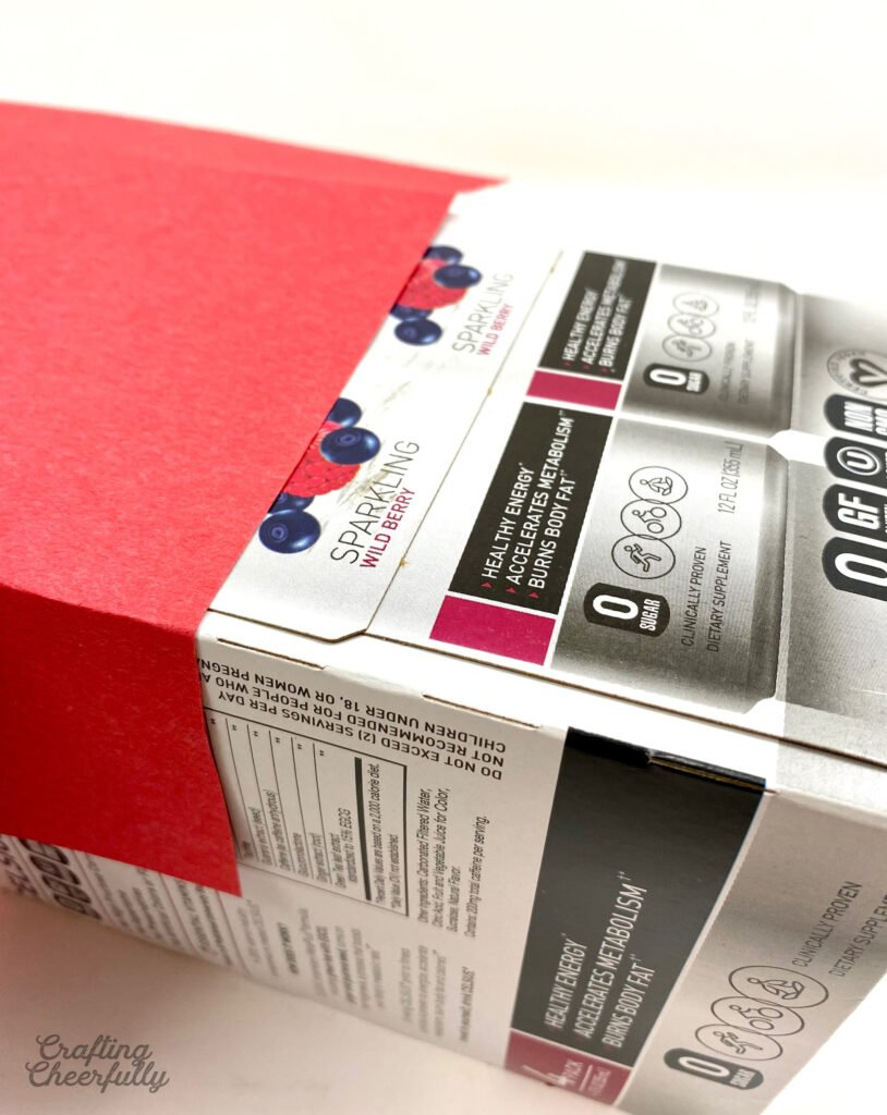 Red construction paper is folded over the sides of the cardboard box.