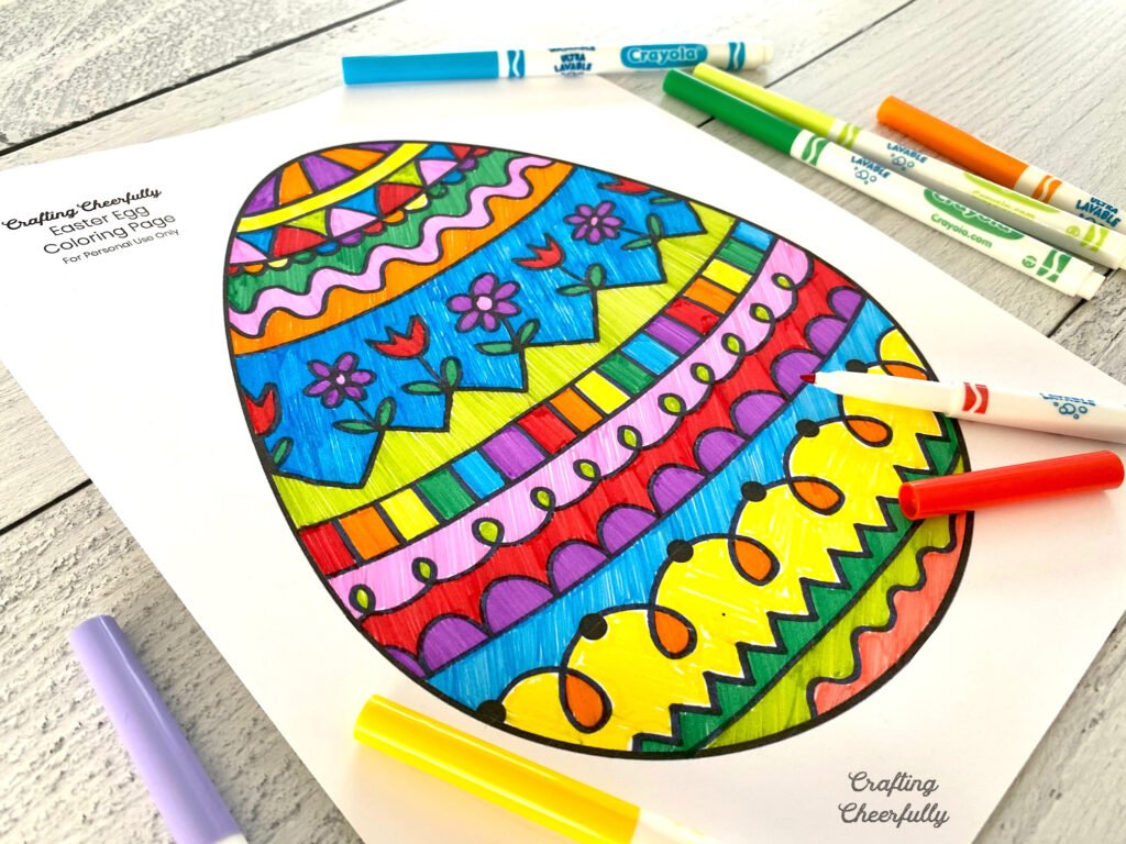 Colorful easter egg coloring page with markers lay on a wooden tabletop.