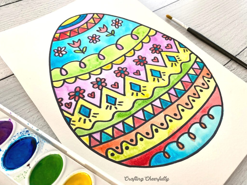 Easter egg coloring page with watercolor paints.