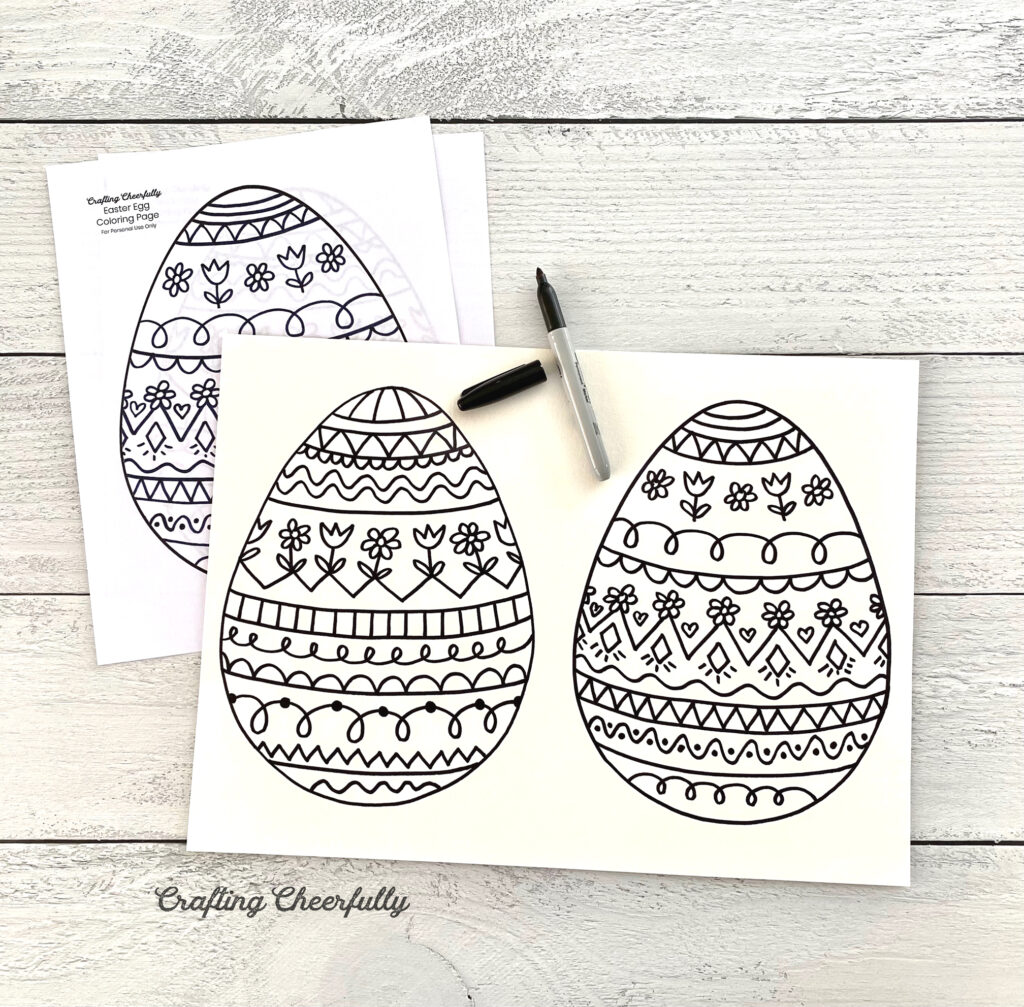 Easter egg doodles traced onto a sheet of watercolor paper sit on a wooden tabletop.