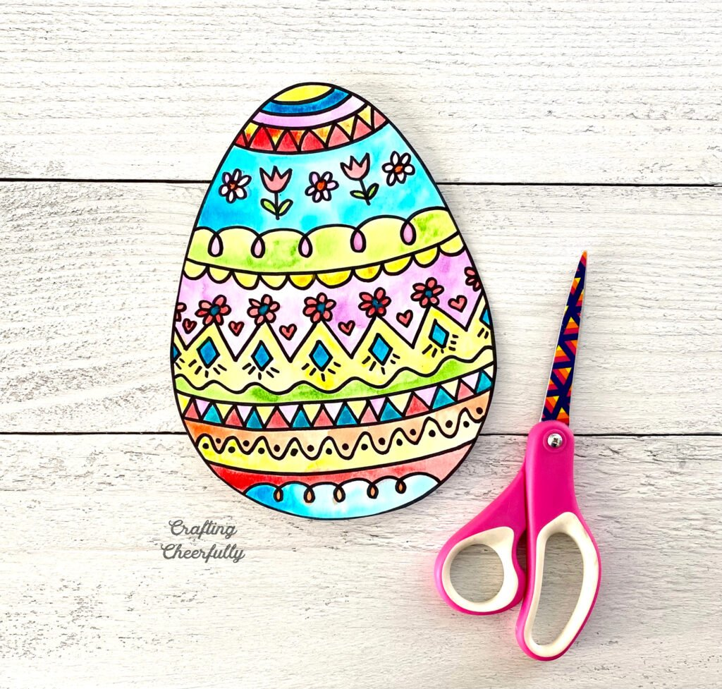 Cut out doodled Easter egg sits next to a scissors on a wooden table.