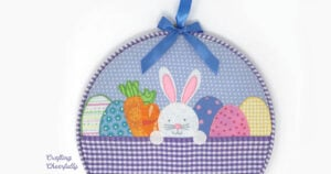 Easter embroidery hoop with small white rabbit and colorful easter eggs in a purple basket.