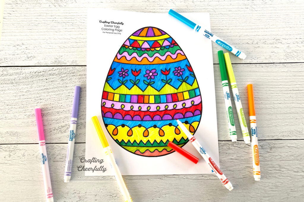 Patterned Easter egg coloring page with markers lay on a wooden table top.