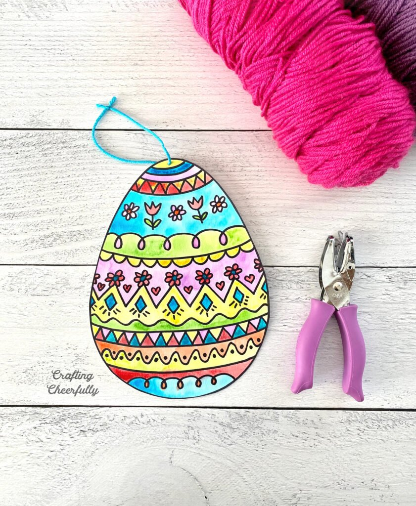 Doodle easter egg painting sits next to a hole punch and yarn on a wooden table top.