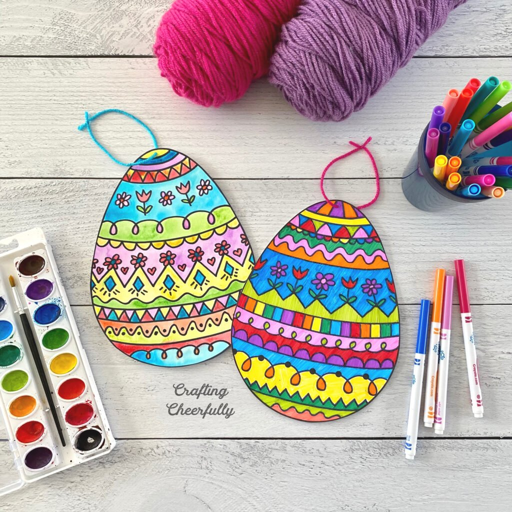 Easter Egg coloring pages lay on a wooden table with watercolor paint, markers and yarn.