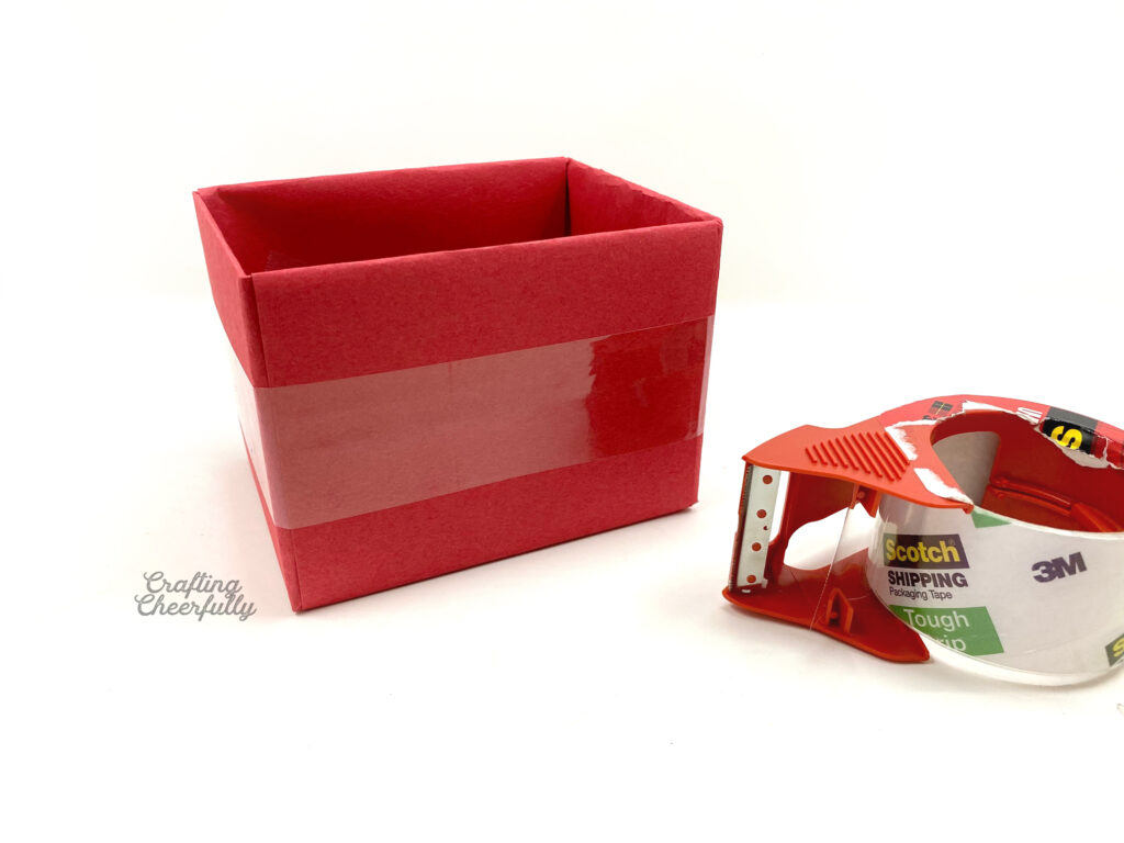 Clear packing tape is laying next to a red box.