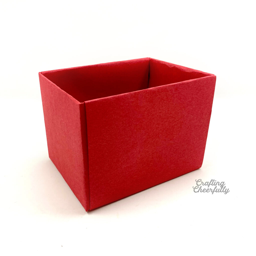 A box covered in red construction paper sits on a white table.