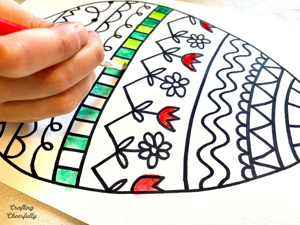 A hand is seen painting a doodled Easter egg coloring page.