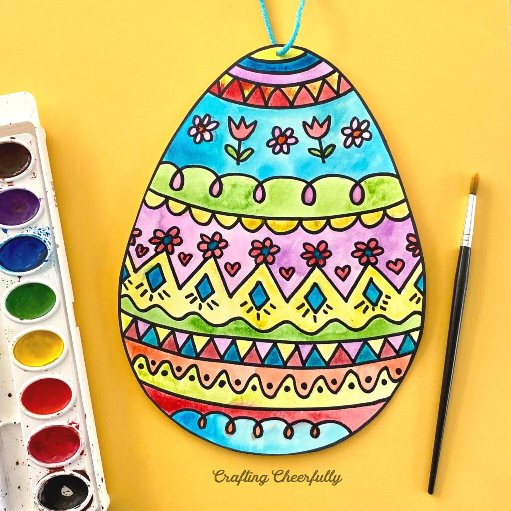 Colorful Easter eggs with cute doodles lays on a yellow background with watercolor paints and paintbrush.
