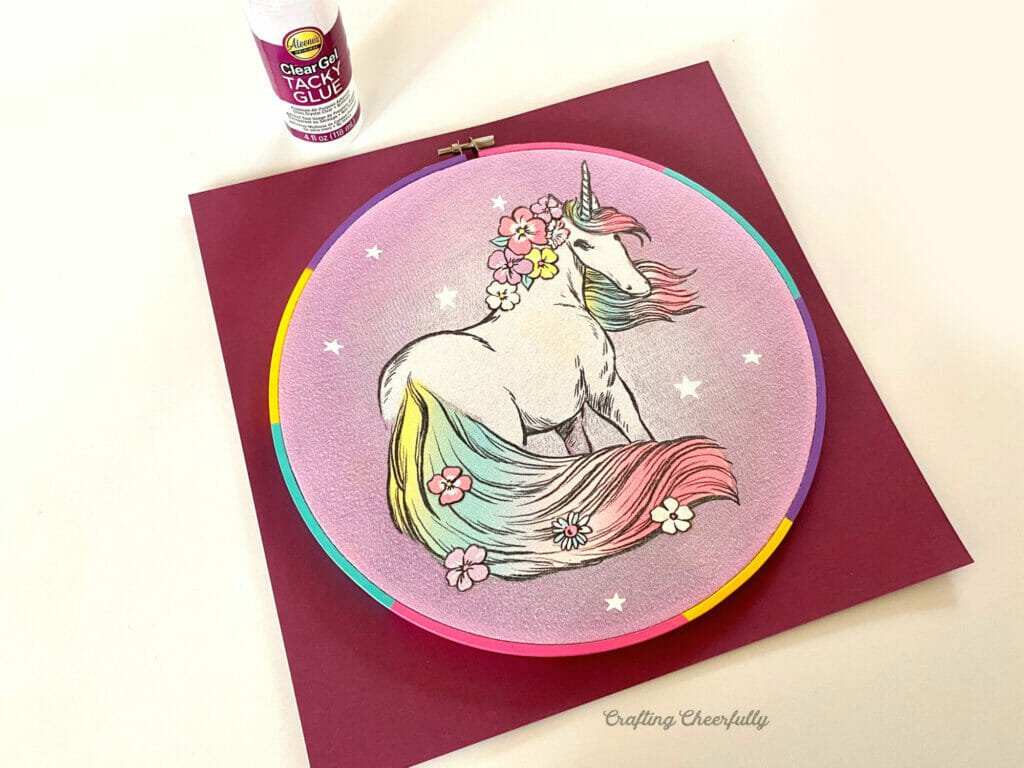 Embroidery hoop with unicorn in it laying on top of a piece of paper with a bottle of tacky glue next to it.