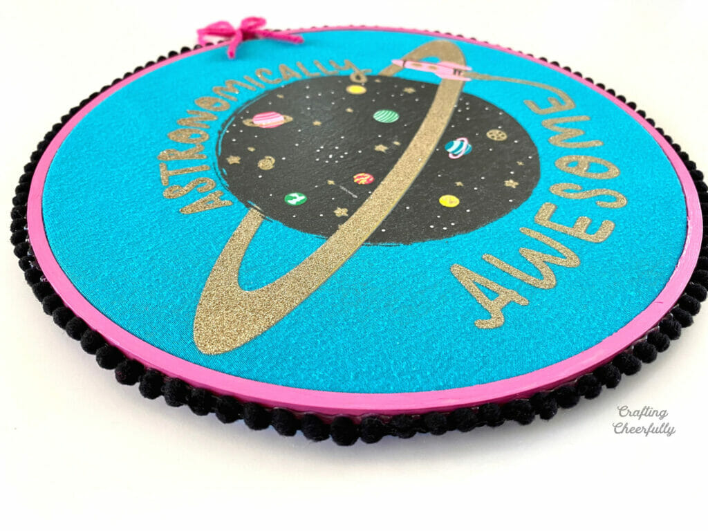 An embroidery hoop with black pom pom trim attached around the edges.