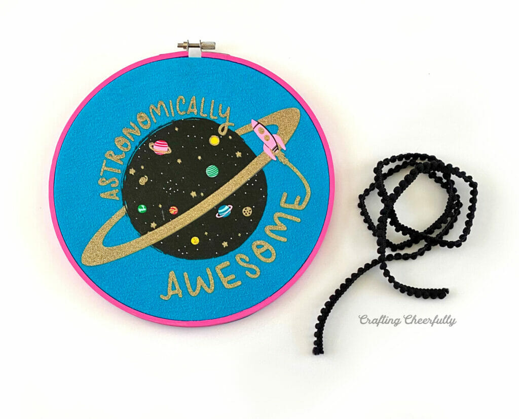 Embroidery hoop with a space t-shirt featured inside of it and black pom pom trim laying next to it.