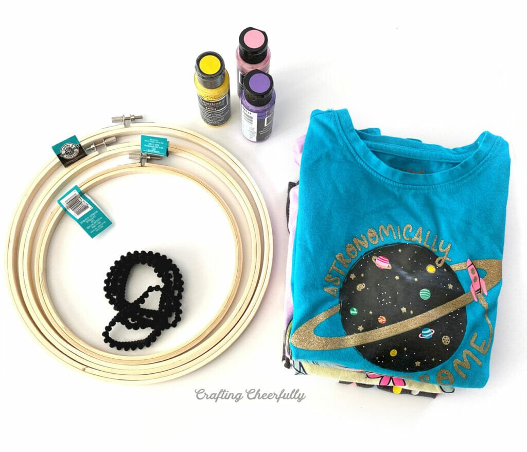 Supplies to make embroidery hoop decor laying on a white table including embroidery hoops, t-shirts, paint bottles and black pom pom trim.