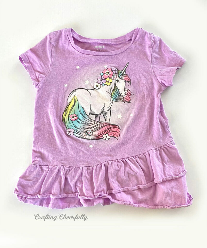 Child's purple t-shirt with a unicorn design on the front.