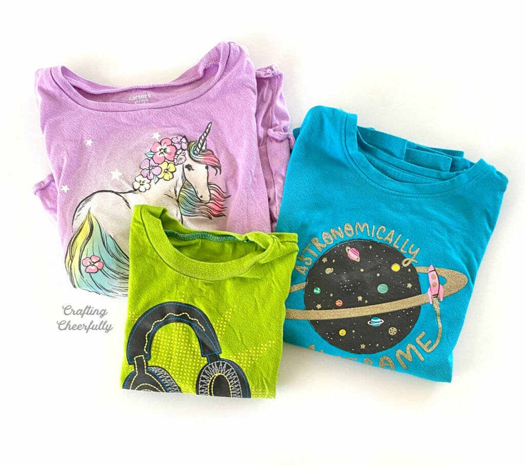 Three colorful children's t-shirts lay on a white table.