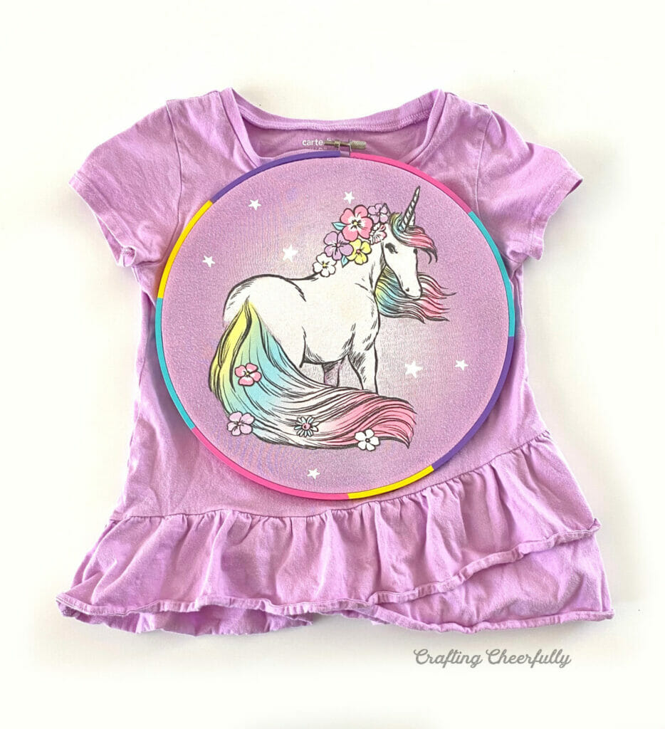 Child's purple t-shirt with a unicorn on the front pushed through an embroidery hoop.