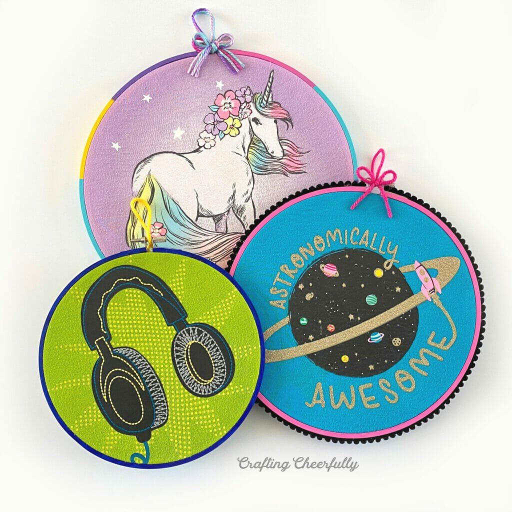 Three embroidery hoops filled with graphics from old clothing.