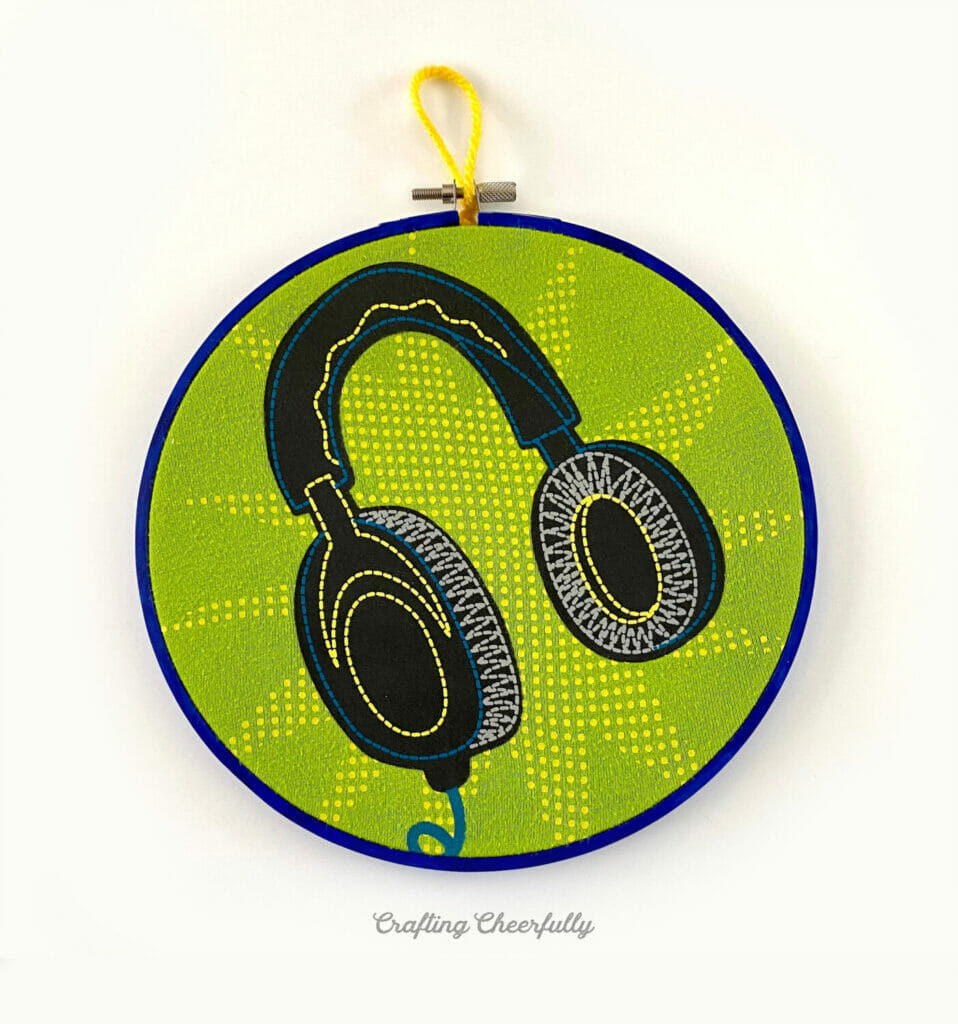 Embroidery hoop with headphones featured inside of it.