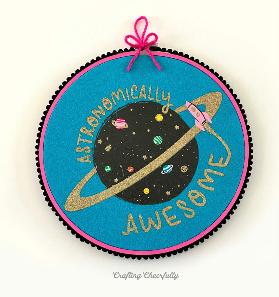 "Embroidery hoop painted pink with blue space shirt inside with the words ""Astronomically Awesome"" on it."