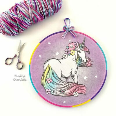 Embroidery hoop decor made with a children's t-shirt with a unicorn on it.