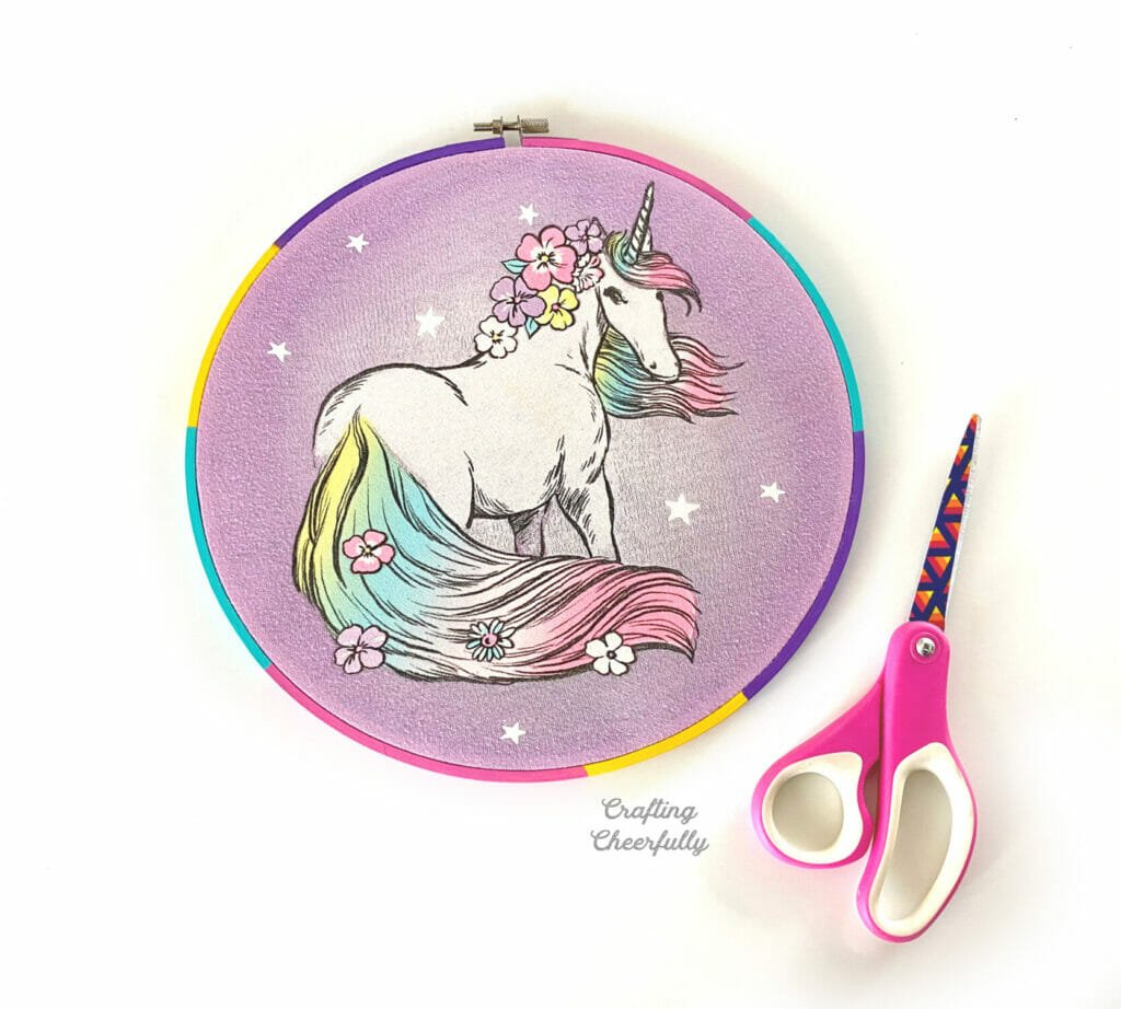 Unicorn embroidery hoop with a scissors next to it.