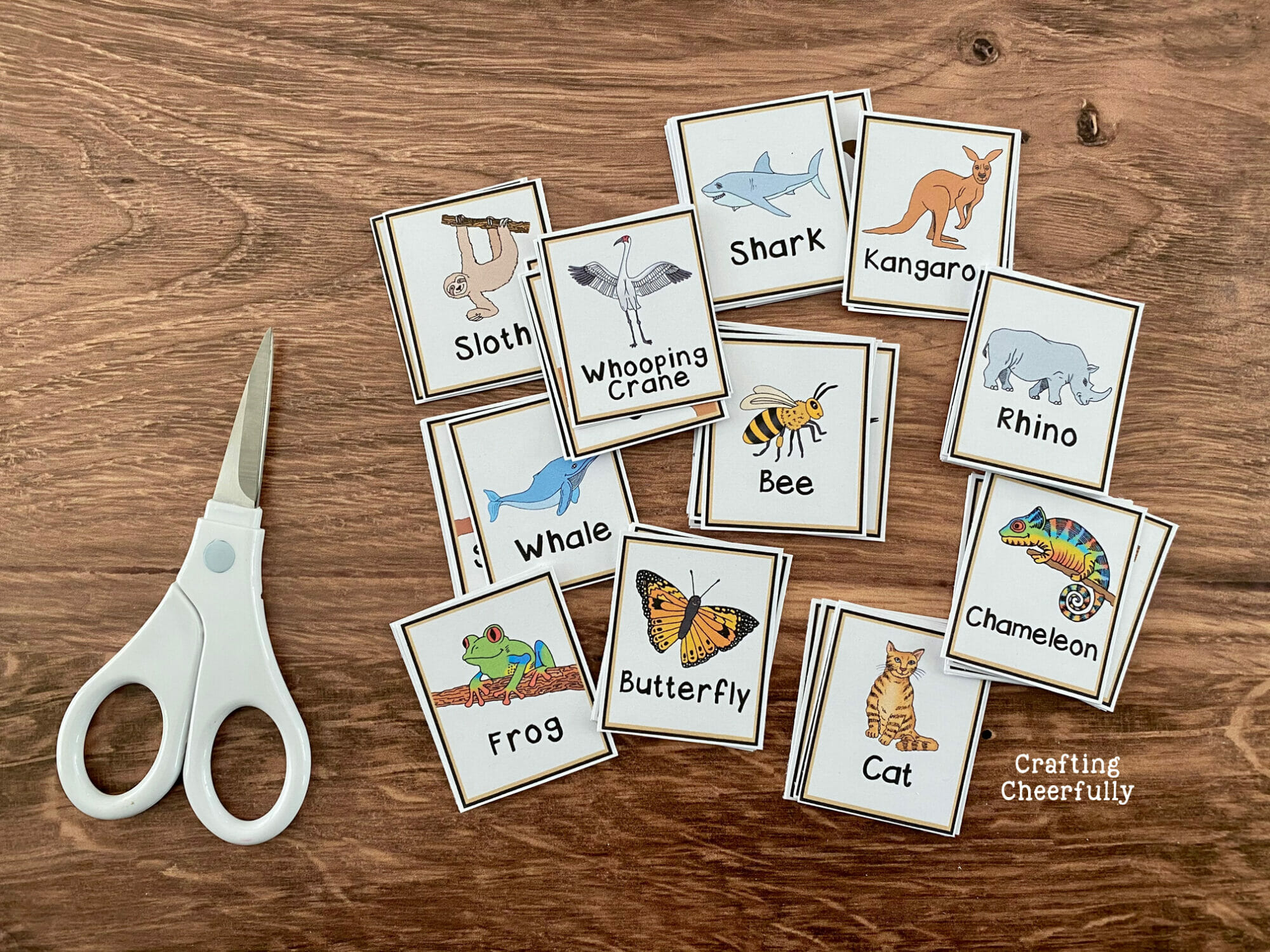 Calling cards for Animal BINGO lay on a table with a white scissors.